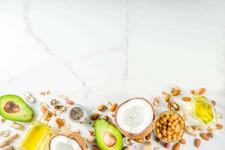 Gesunde vegane Fettnahrungsquellen, Omega3-, Omega-6-Zutaten - Mandeln, Pekannüsse, Haselnüsse, Walnüsse, Olivenöl, Chiasamen, Avocado, Kokosnuss, dunkelgrüner Hintergrundkopierraum