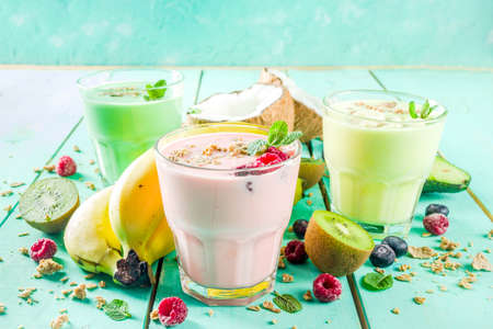 Summer refreshing drinks - protein shakes, milkshakes or smoothies, with fresh berry and fruits, light blue table copy space