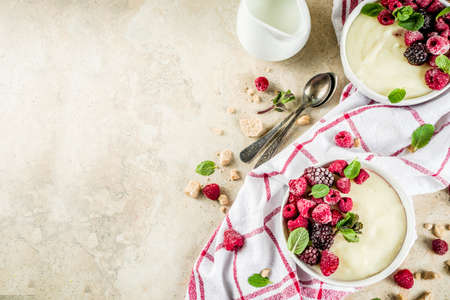 Two bowl with Semolina porridge with fresh berries, beige stone table copy space top view 스톡 콘텐츠 - 116162187