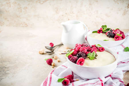 Two bowl with Semolina porridge with fresh berries, beige stone table copy space top view