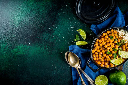 Vegan indian food, Sweet Potato and Chickpea curry, Chana Masala, with lime slices and spices on dark green stone table top ciew copy space Archivio Fotografico - 116162416