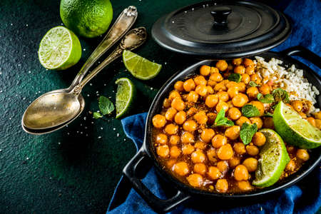 Vegan indian food, Sweet Potato and Chickpea curry, Chana Masala, with lime slices and spices on dark green stone table top ciew copy space Stock fotó