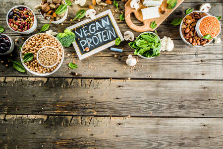 Healthy plant vegan food, veggie protein sources: Tofu, vegan milk, beans, lentils, nuts, soy milk, spinach and seeds. Old wooden background copy space 写真素材