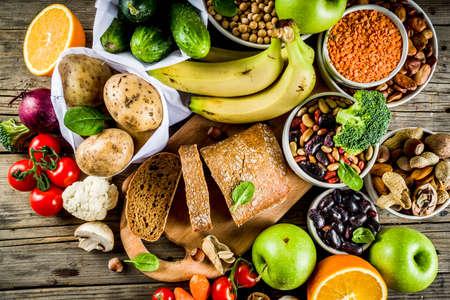 Gezond eten. Selectie van goede koolhydraatbronnen, vezelrijk voedsel. Een dieet met een lage glycemische index. Verse groenten, fruit, granen, peulvruchten, noten, groenten. Houten achtergrond kopie ruimte