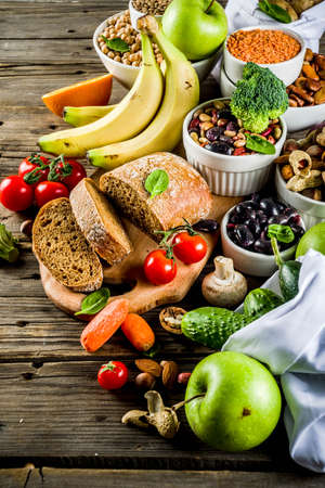 Healthy food. Selection of good carbohydrate sources, high fiber rich food. Low glycemic index diet. Fresh vegetables, fruits, cereals, legumes, nuts, greens. Wooden background copy space