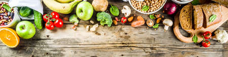 Healthy food. Selection of good carbohydrate sources, high fiber rich food. Low glycemic index diet. Fresh vegetables, fruits, cereals, legumes, nuts, greens. Wooden background copy space banner Stock Photo