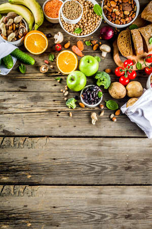 Healthy food. Selection of good carbohydrate sources, high fiber rich food. Low glycemic index diet. Fresh vegetables, fruits, cereals, legumes, nuts, greens. Wooden background copy space Stock Photo - 116433595