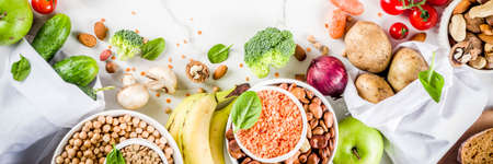 Healthy food. Selection of good carbohydrate sources, high fiber rich food. Low glycemic index diet. Fresh vegetables, fruits, cereals, legumes, nuts, greens. White marble background copy space banner Reklamní fotografie