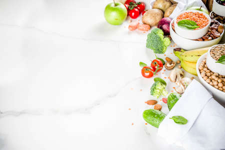 Healthy food. Selection of good carbohydrate sources, high fiber rich food. Low glycemic index diet. Fresh vegetables, fruits, cereals, legumes, nuts, greens. White marble background copy space