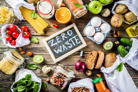 Zero Waste Shopping und nachhaltiges Lifestyle-Konzept, verschiedenes Bio-Gemüse, Getreide, Nudeln, Eier und Obst in wiederverwendbaren Supermarkttüten. Kopierraum Draufsicht, Holzhintergrund