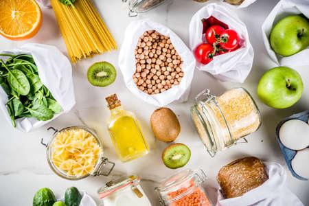 Achats zéro déchet et concept de mode de vie durable, divers légumes biologiques de la ferme, céréales, pâtes, œufs et fruits dans des sacs de supermarché d'emballage réutilisables. copie espace vue de dessus, table en béton blanc