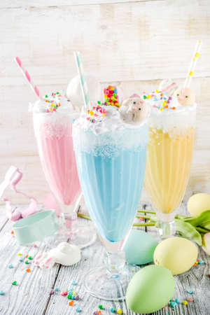 Funny easter food, ideas recipes for children Easter party, colorful blue yellow pink milkshakes with sugar sprinkles, wooden background with Easter egg and bunny rabbit decoration, copy space