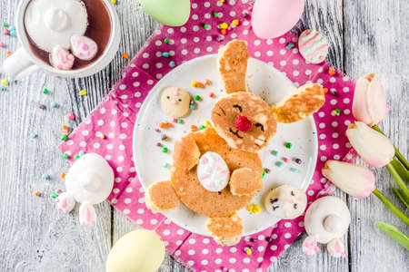 Funny easter breakfast food, kids pancake in form of bunny rabbit, with hot chocolate, top view wooden background copy space