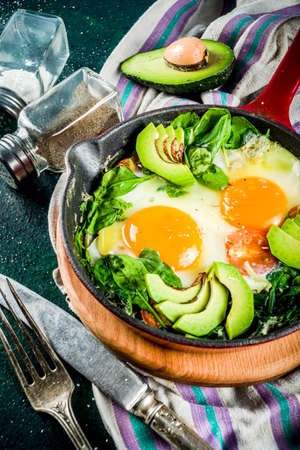Green vegetable shakshuka. Middle eastern traditional dish shakshouka. Fried eggs with tomatoes, baby spinach, vegetables and herbs, Dark green background top view.