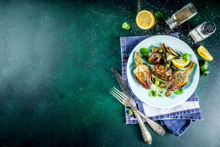 Cooked baked artichoke, alla romana, grilled artichoke flowers with olive oil, lemon, garlic, mint and spices. Copy space Reklamní fotografie