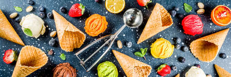 Colorful fruit and berry, nut, chocolate and vanilla ice cream, with waffle ice-cream cones, with fresh fruit and berries, top view copy space banner