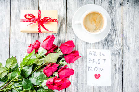 Mothers day greeting background concept, with red rose flowers, greeting card For best Mom wooden calendar and coffee mug, wooden background copy space