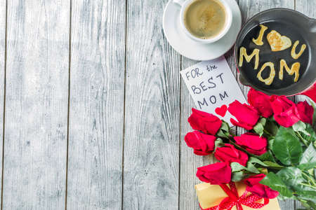 Mothers day greeting background concept, with red rose flowers, greeting card creative pancakes for best mom, i love mom, and coffee mug, wooden background copy space