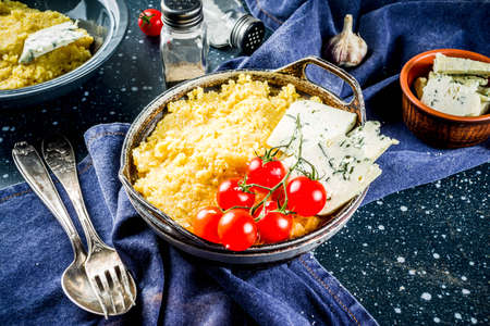 Lombardy italian food, Polenta corn porridge with tomatoes  with gorgonzola cheese, dark blue background copy space