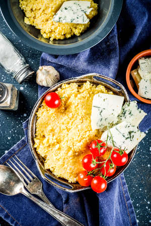 Lombardy italian food, Polenta corn porridge with tomatoes  with gorgonzola cheese, dark blue background copy space