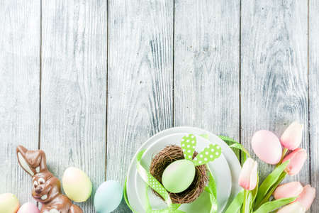 Easter holiday table setting with rabbits and eggs, plates with colorful eggs and chocolate bunny rabbits, festive ribbon, wooden background top view copy space Stock Photo