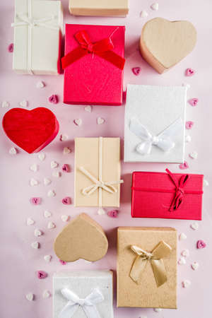 Valentines day gifts boxes background, frame for holiday greeting card background, with confetti  candy hearts, flat lay, top view, copy space