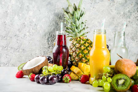 Different fruit juices smoothies concept, summer vitamins diet, with tropical fruits and berries on a light background, Stockfoto