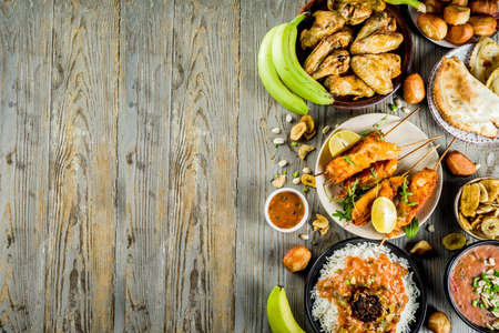 West african food concept. Traditional Wset African dishes assortment - peanut soup, jollof rice, grilled chicken wings, dry fried bananas plantains, nigerian chicken kebabs, meat pies, top view Imagens