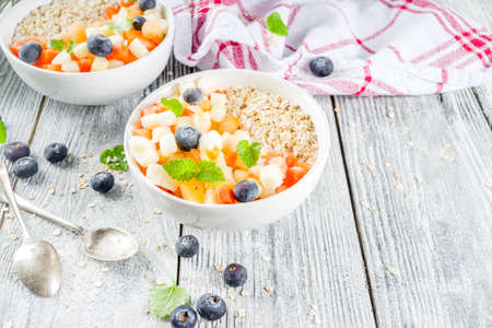 Healthy breakfast oatmeal with tropical fruits and berries, on white wooden background copy space