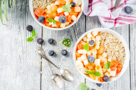Healthy breakfast oatmeal with tropical fruits and berries, on white wooden background copy space Stock Photo - 117254715