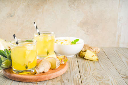 Healthy and immunity diet drink. Ginger and pineapple cold tea, infused water, Wooden background copy space