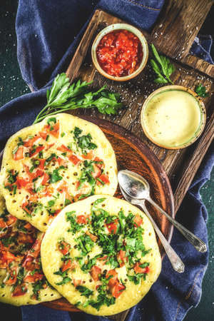 Indian traditional food recipes, Uttapam oats or semolina pancakes with fresh vegetables and herbs, dark blue background copy space top view Zdjęcie Seryjne
