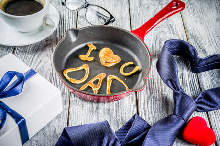 Father's day holiday concept, greeting card background with presents and pancakes letter inscription For best father, I love you dad, wooden background copy space top view