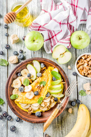 Healthy breakfast food, Sweet stuffed egg omelette with fruits, berries and nuts, rustic wooden background copy space top view Stock Photo