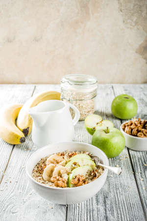 Healthy breakfast oatmeal with nuts ad fruits - apple, banana, walnuts, With milk on wooden background copy space