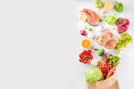 Concept d'achat d'aliments sains, ingrédient de régime équilibré - viande, poisson, fruits, légumes. Aliments frais avec sac à provisions en papier, vue de dessus sur l'espace de copie de fond blanc