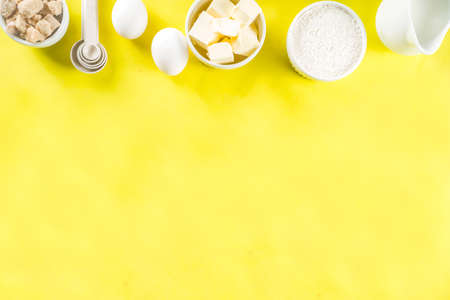 Baking ingredients and tools on trendy bright yellow background - flour, eggs, sugar, milk, butter, layout, flatlay top view copy space 版權商用圖片