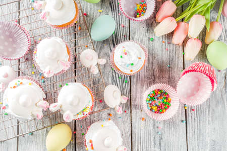 Easter kids party treat. Festive Easter food. Homemade cupcakes with cream and marshmallow cute bunny rabbits with paws. On a white wooden table, top view copy space