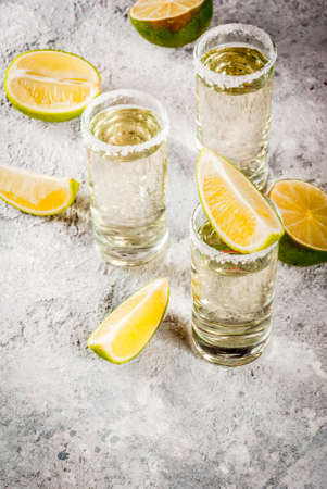 Tequila shots with lime and sea salt on grey stone table, copy space