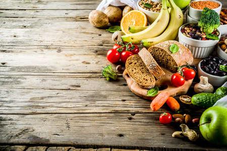 Cibo salutare. Selezione di buone fonti di carboidrati, alimenti ricchi di fibre. Dieta a basso indice glicemico. Verdure fresche, frutta, cereali, legumi, noci, verdure. Spazio di copia di sfondo in legno