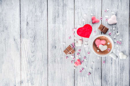 Valentines day treat ideas, two cups hot chocolate drink with marshmallow hearts red pink white color with chocolate pieces, sugar sprinkles, old wooden background copy space top view 写真素材