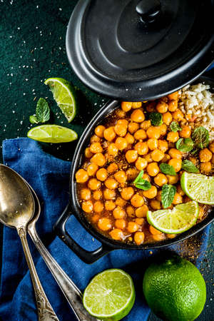 Vegan indian food, Sweet Potato and Chickpea curry, Chana Masala, with lime slices and spices on dark green stone table top ciew copy space Stock Photo