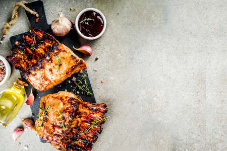 Grilled meat concept. bbq pork ribs with barbeque sauce, olive oil. fresh herbs on grey stone background copy space
