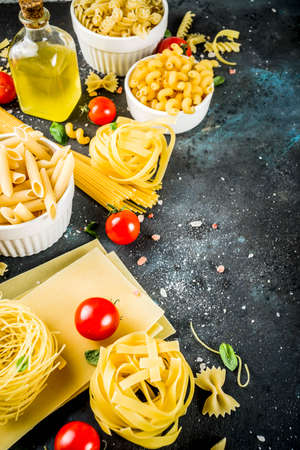 Italian food concept, various raw pasta assortment - spaghetti, lasagna, fusilli, tagliatelle, penne, tortellini, ravioli, with tomatoes and basil leaves dark background copy space top view