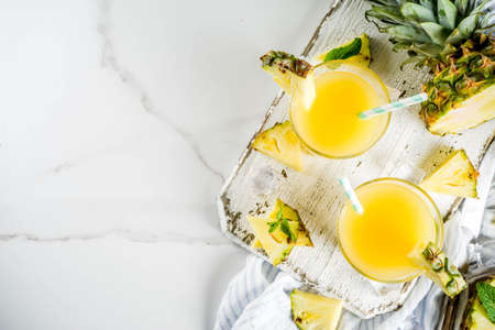 Fresh pineapple juice or cocktail, with pieces of fresh pineapple, ice, decorated with mint, on a white marble table, copy space top view