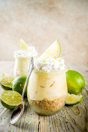 Homemade no baked cheesecake. key lime pie in small portioned jars, wooden background copy space