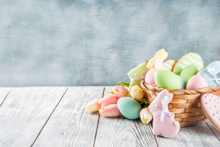 Easter greeting card background with pastel colored eggs and homemade cookies shaped in eggs and bunnies rabbits. With a basket, tulips, rustic wooden table, copy space Reklamní fotografie - 118535177