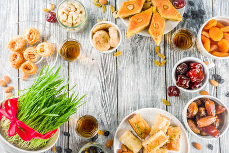Happy Nowruz holiday background. Celebrating Nowruz sweets and treats- baklava, various dried fruits,  nuts, seeds, wooden background with green grass, copy space top view 版權商用圖片 - 118617213