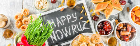 Happy Nowruz holiday background. Celebrating Nowruz sweets and treats- baklava, various dried fruits,  nuts, seeds, wooden background with green grass, copy space top view banner
