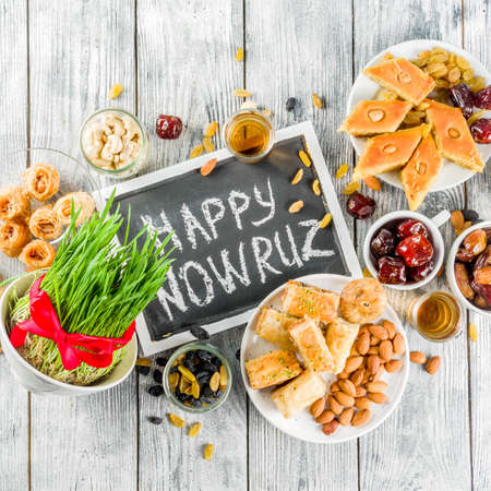 Happy Nowruz holiday background. Celebrating Nowruz sweets and treats- baklava, various dried fruits,  nuts, seeds, wooden background with green grass, copy space top view square 版權商用圖片
